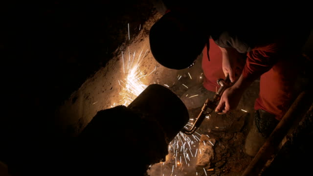 A high angle shot at night and a worker fine cutting a ruptured pipe in order to weld it together with a new pipe video