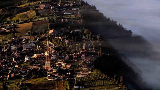 High angle shot Fog over top Cemoro Lawang near at mount bromo video