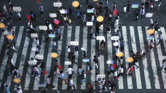 vidéos et rushes de tir d'angle élevé d'un passage pour piétons bondé dans la grande ville. réalité augmentée des signes, symboles, suivis de localisation et emojis des médias sociaux sont ajoutés aux personnes. concept de technologie future. - réseautage