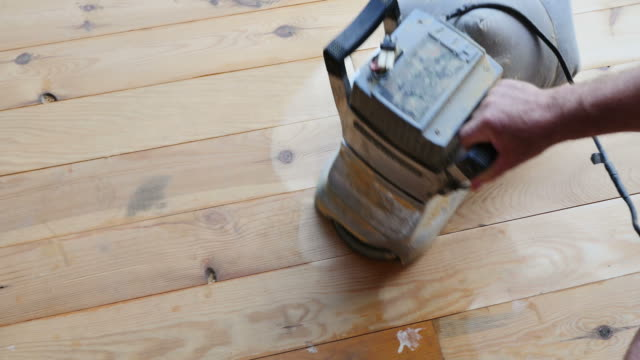 A high angle shot of a man sandering a parquet with a sandering machine video