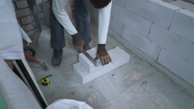 high angle shot of builder sawing aerated concrete block after measuring it