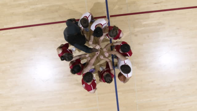 High angle shot of coed sports team huddle High angle shot of a coed sports team huddling on a basketball court high school sports stock videos & royalty-free footage