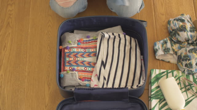 High Angle Shot Of Woman Packing Suitcase For Beach Vacation video