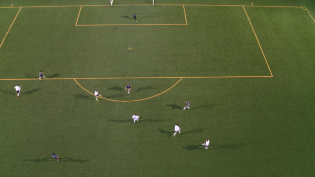 High angle soccer player scoring on opponents High angle drone shot of a soccer player dribbling past the defenders and scoring on the apposing team match sport stock videos & royalty-free footage