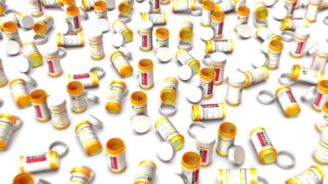 high angle up from single empty pill bottle revealing many - amfetamin pills bildbanksvideor och videomaterial från bakom kulisserna
