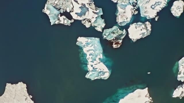 высокоугольный видео ледниковых айсбергов, плавающих в лагуне в исландии - ледник стоковые видео и кадры b-roll