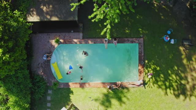 vídeos y material grabado en eventos de stock de vista de vídeo de gran angular de la familia disfrutando de la piscina del patio trasero - backyard pool
