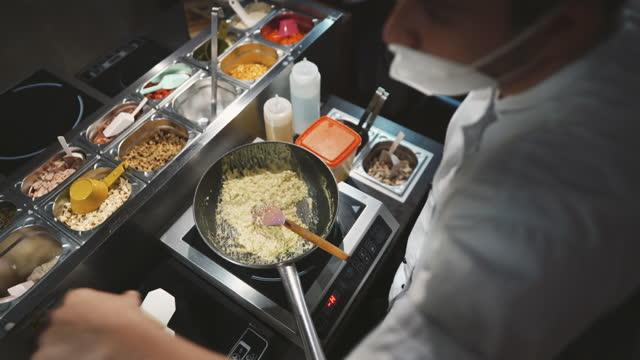 コロナウイルスパンデミック中の男性シェフ料理の高角度図 - 料理人点の映像素材/bロール