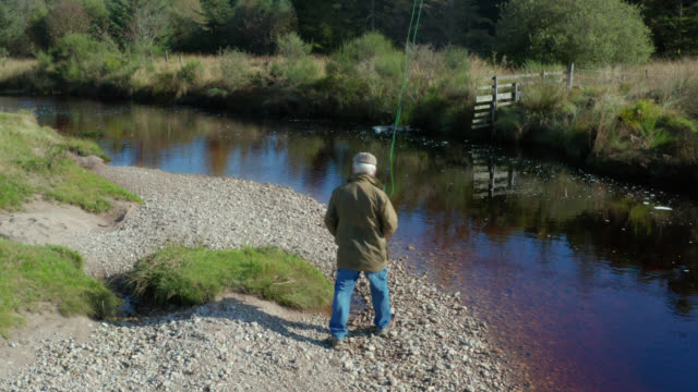 High angle view of a senior man on riverbank with a fly fishing rod video