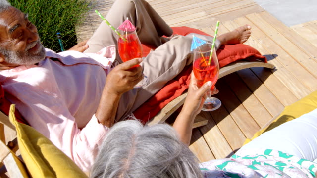 High angle view of black senior couple relaxing on pool deck chair in back yard of their home 4k