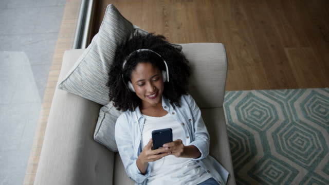 High angle view of black woman relaxing on couch listening music with headphones and using smartphone looking very happy High angle view of black woman relaxing on couch listening music with headphones and using smartphone looking very happy - Lifestyles listening stock videos & royalty-free footage