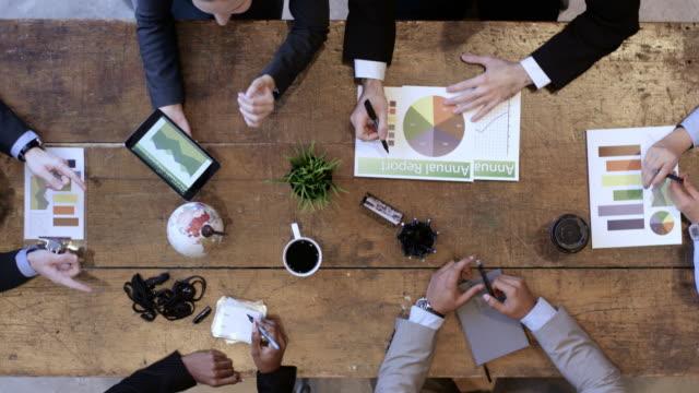 hohe winkelansicht des business development teams im strategietreffen - konferenztisch stock-videos und b-roll-filmmaterial