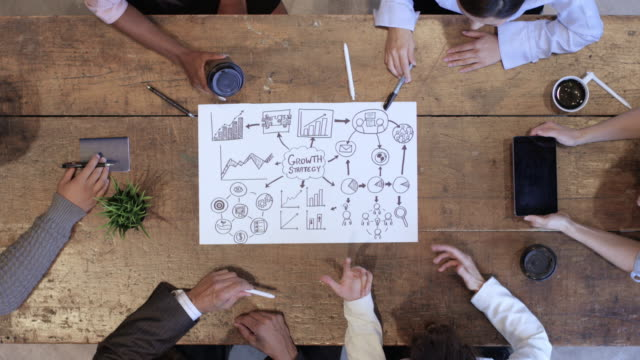 high angle view des business development teams im strategiemeeting - konferenztisch stock-videos und b-roll-filmmaterial