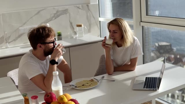 High angle view of couple smiling with joy at good morning in modern kitchen, affectionate young married couple drinking milk, having breakfast together in their apartment kitchen video