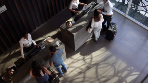 High angle view of couples checking into hotel at the front desk High angle view of couples checking into hotel at the front desk all looking very happy service stock videos & royalty-free footage