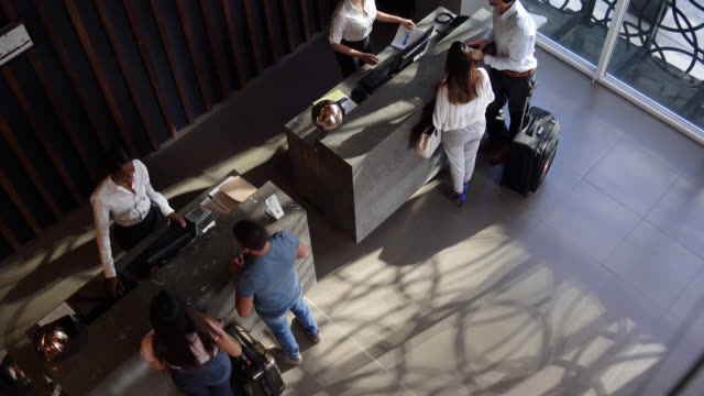 high angle view of couples checking into hotel at the front desk - business travel stock videos and b-roll footage
