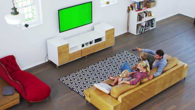 vídeos y material grabado en eventos de stock de vista de ángulo alto de familia sentado en el sofá en el salón viendo la televisión - family watching tv