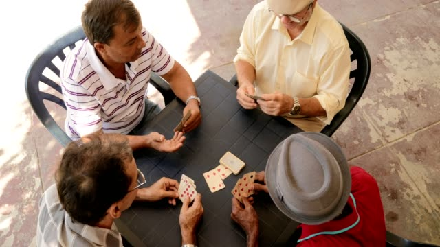 High Angle View Of Friends Men People Playing Cards Happy active retired people, old hispanic friends and free time, senior latino men having fun and playing game of cards at home. Leisure, recreation, retirement. High angle view of table playing card stock videos & royalty-free footage