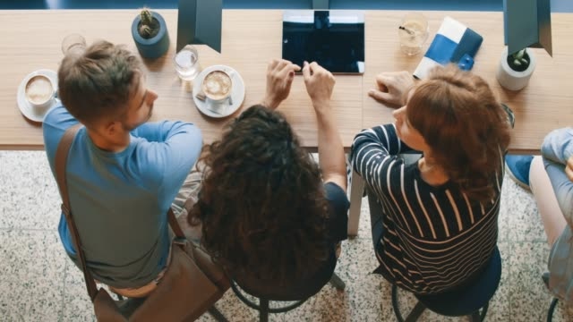 high angle view of friends sitting in cafe - caffetteria video stock e b–roll