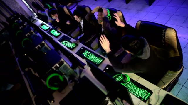 High angle view of gamers winning in eSport match in internet game cafe High angle view of five gamers winning in eSport match in internet game cafe. match sport stock videos & royalty-free footage