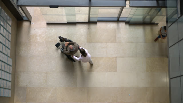 High angle view of healthcare professionals and people walking in and out of hospital