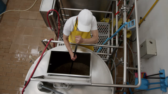 High angle view of man cleaning a distillery tank at a brewery factory