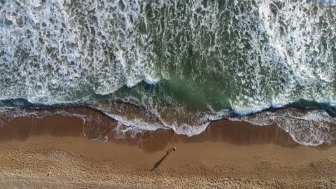 wysoki kąt widzenia człowieka jogging na plaży - piękno filmów i materiałów b-roll