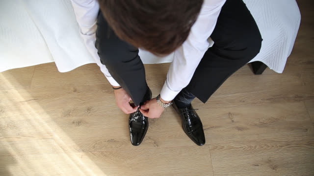 vista ad alto angolo dell'uomo che lega i lacci delle scarpe - scarpe video stock e b–roll