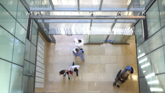 High angle view of people and healthcare professionals walking in and out of the hospital