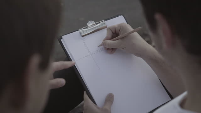 High angle view of two young Caucasian men drawing scheme outdoors. Unrecognizable engineers planning design. Professions and creativity concept