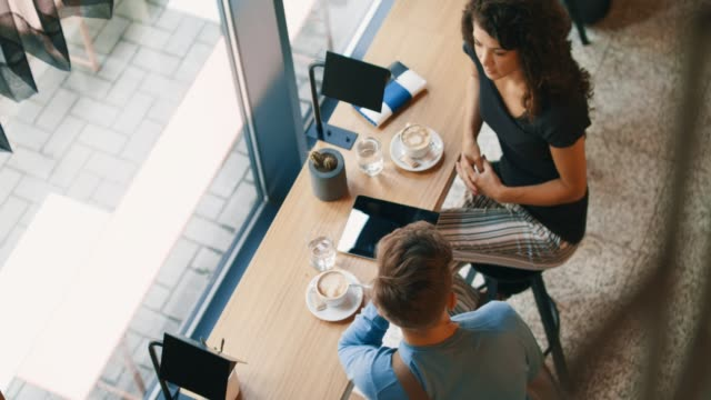 vídeos de stock e filmes b-roll de high angle view of young couple in cafe - coffee table