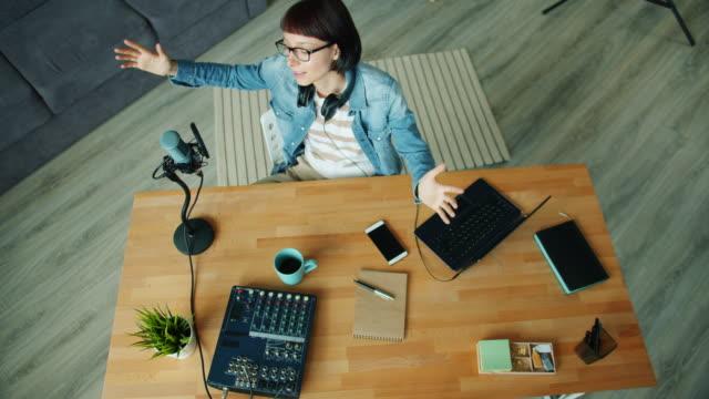 vídeos de stock, filmes e b-roll de opinião de ângulo elevado a senhora nova que fala no microfone que gesticula no estúdio - podcast