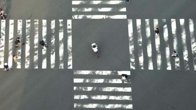 東京・銀座の夏の日の午後、道路に影を落とし、横断歩道を歩く男女の歩行者群の4kハイアングルビューワイドショット。 - 交差点点の映像素材/bロール