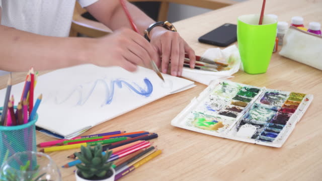 high angle vivew of watercolor paint and equipment such as paintbrush and part Asian handsome man painting one paper page with watercolor to create artist skill and imagination. Concept of young adult and leisure activity at the weekend.