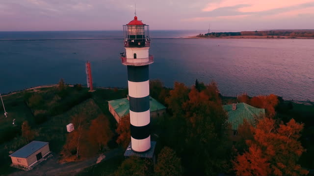 vídeos de stock e filmes b-roll de high beacon on the beach at the evening sunset - aerial view - barragem do roxo