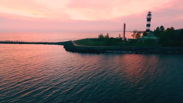 faro alto sulla spiaggia al tramonto serale - vista aerea - lettonia video stock e b–roll