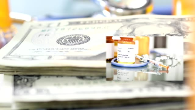 vídeos de stock e filmes b-roll de high cost of healthcare. us currency, prescription medicines, stethoscope. - medicare