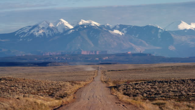 High Desert Plains Outside of Moab, Utah with a Vanishing Point Dirt Road Leading to Majestic Snowcapped Mountains