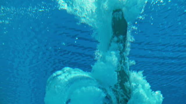 slo mo ld high diver doing an underwater flip when hitting the pool - tuffarsi video stock e b–roll