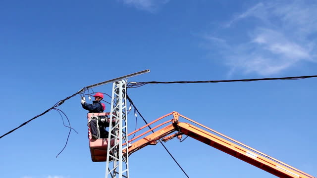 High elevated cherry picker with team of electrician's who are working on power line, pole video