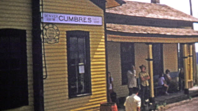 1973: High elevation train station conductor takes tickets and steam locomotive front. video
