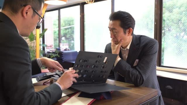 顧客に話している高級テーラー - オペレーター 日本人点の映像素材/bロール
