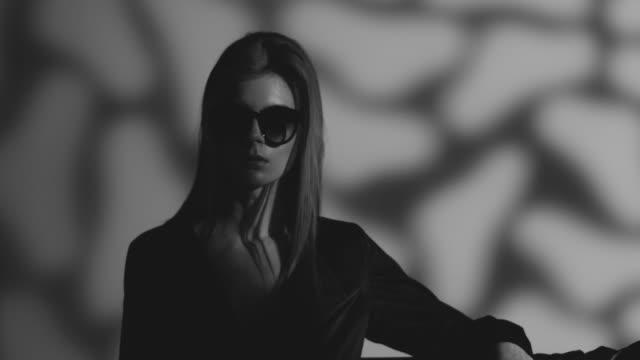 vidéos et rushes de modèle haute couture blond à lunettes, vêtu de noir se déplace. mode vidéo. noir et blanc. - image en noir et blanc