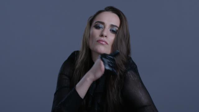 la modella di alta moda vestita di nero con guanti di pelle nera muove le mani. video di moda. - arto umano video stock e b–roll