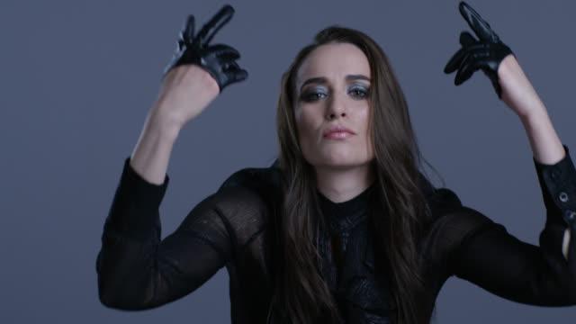 vidéos et rushes de modèle de haute couture vêtue de noir en blouson de cuir noir déplace ses mains. mode vidéo. - crayon à lèvres