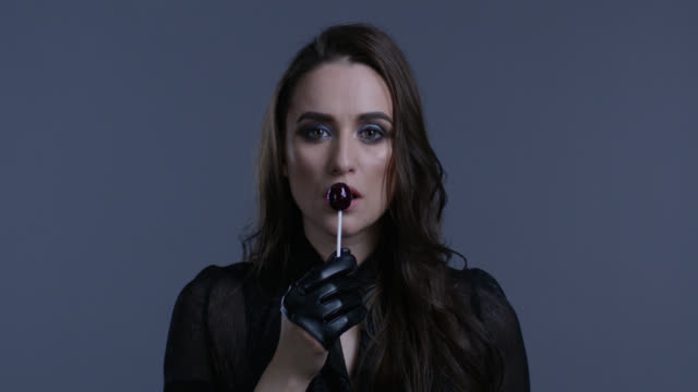 High fashion model holds lollypop in her hand, licking it. Fashion video.