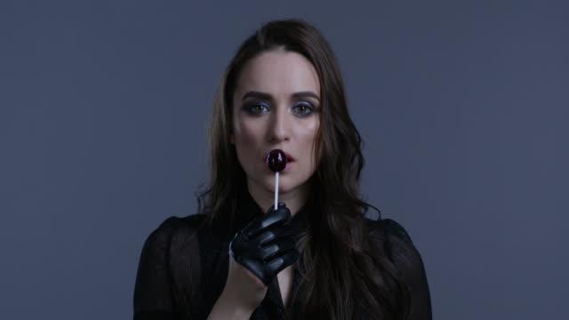 高時尚模特手裡握著棒糖, 舔著它。時尚視頻。 - 波板糖 個影片檔及 b 捲影像