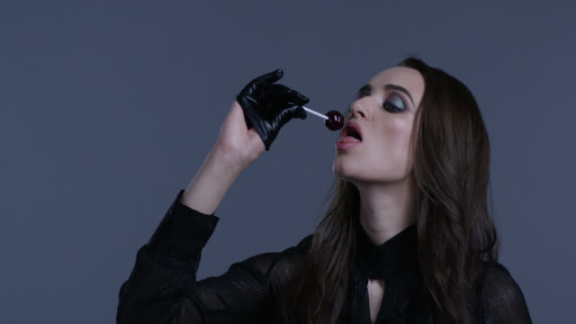 High fashion model holds lollypop in her hand, licking it. Fashion video. High fashion model holds lollypop in her hand, licking it. Fashion video. Slow Motion. 4K 30fps ProRes 4444 lip liner stock videos & royalty-free footage