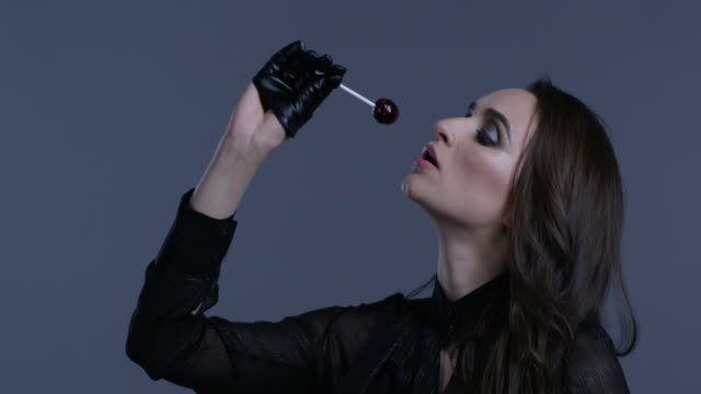 vidéos et rushes de modèle de haute couture détient la sucette dans sa main, il lèche. mode vidéo. - crayon à lèvres