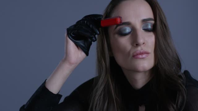 vidéos et rushes de modèle de haute couture détient le rouge à lèvres à la main, de jouer avec lui. mode vidéo. - crayon à lèvres
